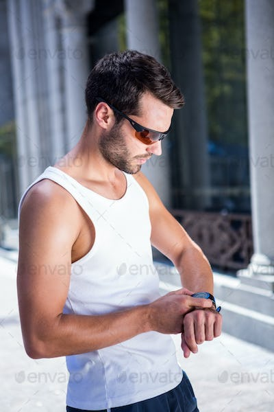 Handsome athlete with sunglasses setting heart rate watch in the city