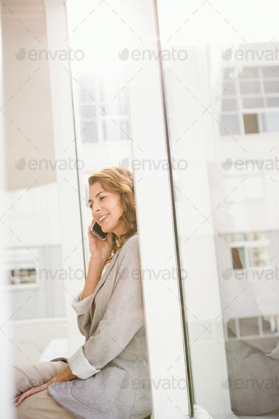 Smiling casual businesswoman having a phone call in the office
