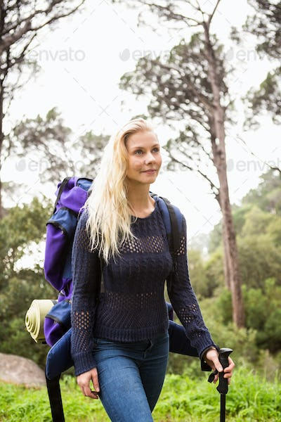 Female hiker walking with a backpack on a crossing path