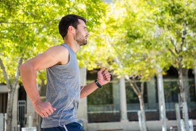 Handsome athlete running in the street on a sunny day
