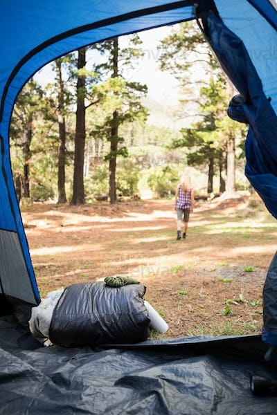 Blonde camper walking away from tent in the nature