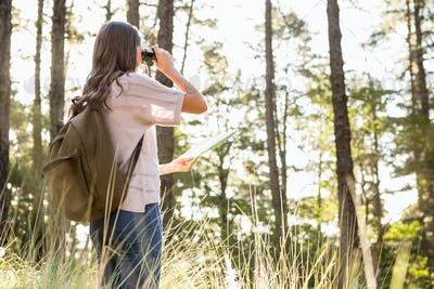 Female hiker looking through the binoculars in the nature