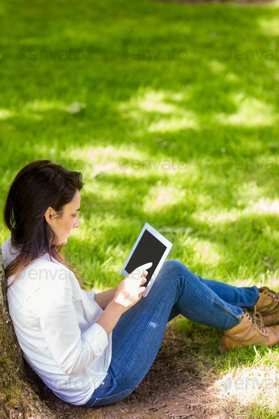 Beautiful brunette using tablet pc in the park on a sunny day