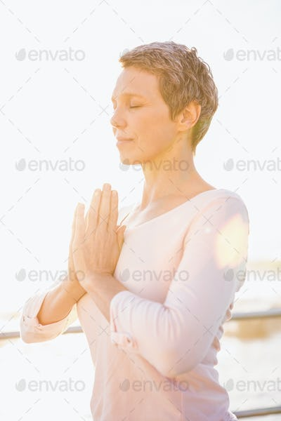 Peaceful sporty woman meditating at promenade on a sunny day