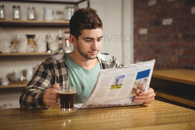Hipster drinking coffee and reading newspaper at coffee shop