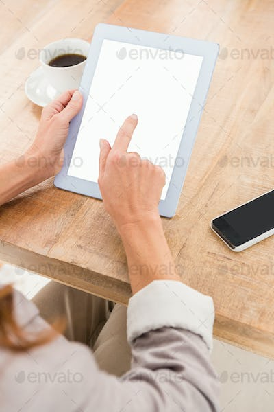 Casual businesswoman using blank screen tablet on wooden desk