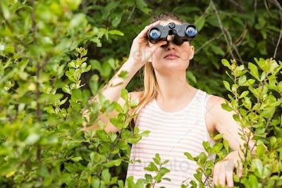 Pretty blonde looking through binoculars in the nature