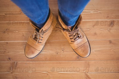 High angle view of woman wearing boots on wooden planks background