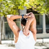 Rear view of athlete stretching his arm in the city