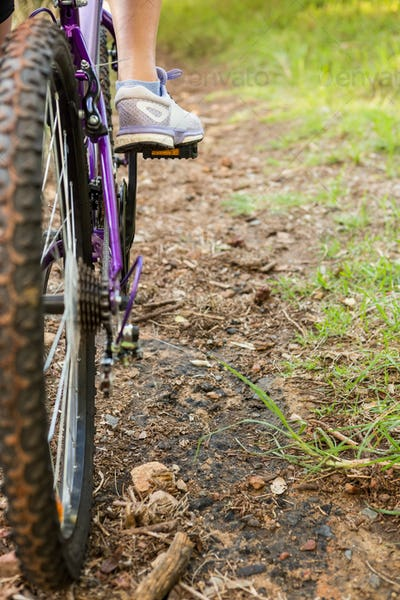 Close up view of woman pedaling on mountain bike in the nature