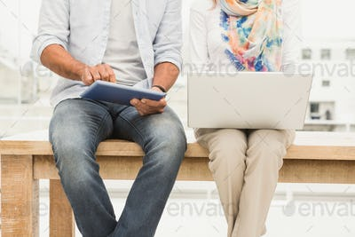 Casual designers sitting on wooden desk and using devices in the office