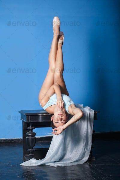 young modern ballet dancer posing on blue background