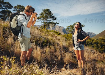 Tourist couple enjoying nature and taking photo
