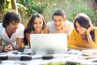 Friends using laptop outdoors