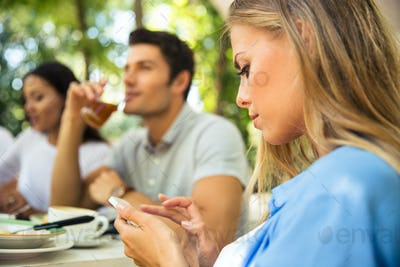 Woman using smartphone while sitting in outdoor restaurant