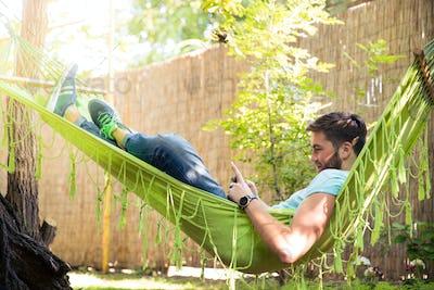 Man using smartphone on hammok