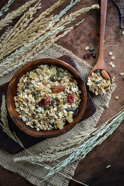 Oat and whole wheat grains flake in wooden bowl on wooden table