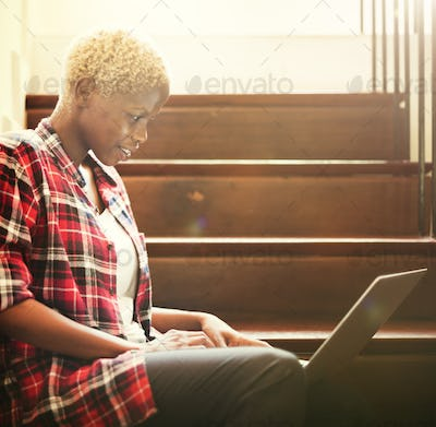 African Woman Searching Internet Sitting on Steps