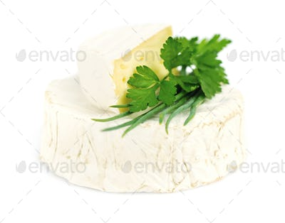 Round camembert cheese with parsley on white background