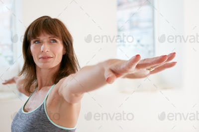 Woman doing Virabhadrasana yoga pose in gym