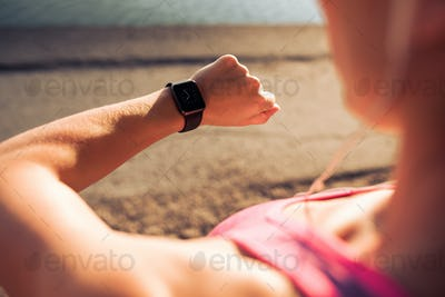 Fitness woman checking time on smartwatch
