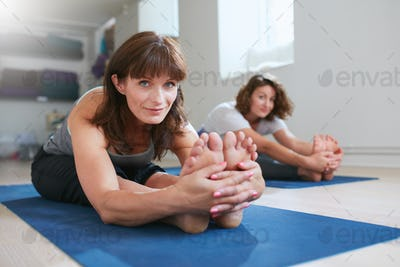 Women doing paschimottanasana yoga pose