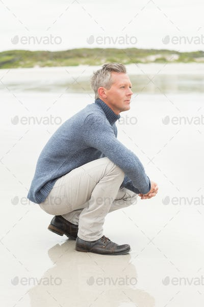 Man crouched down at the shore of the beach