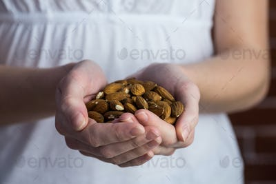 Woman showing handful of almonds in close up