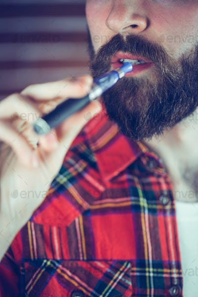 Midsection of man holding electronic cigarette