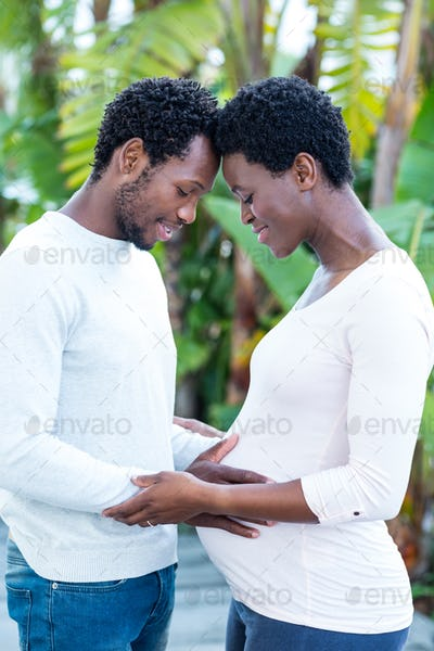 Man touching pregnant wife belly while standing in park