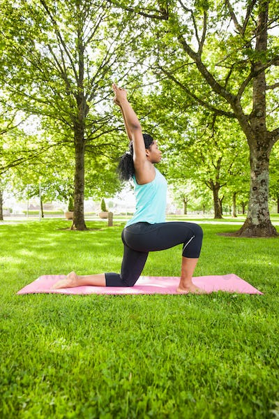 Young woman doing yoga on mat in the park