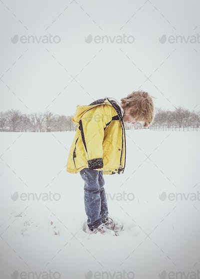 Boy Looking at Feet in the Snow