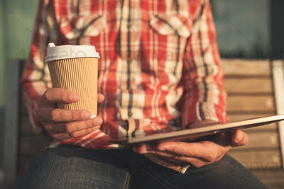 Man holding tablet and cup of coffee