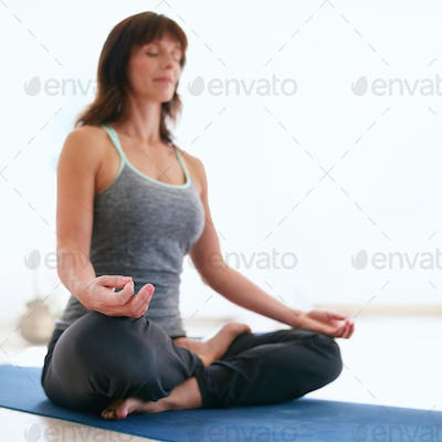 Fitness female relaxing with padmasana yoga workout.