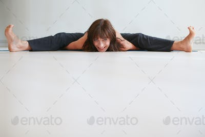 Smiling woman doing splits at gym