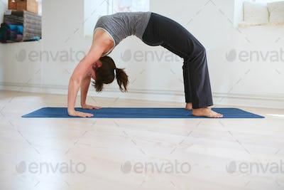 Woman doing yoga - Urdhva Dhanurasana pose