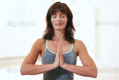 Beautiful woman at gym meditating