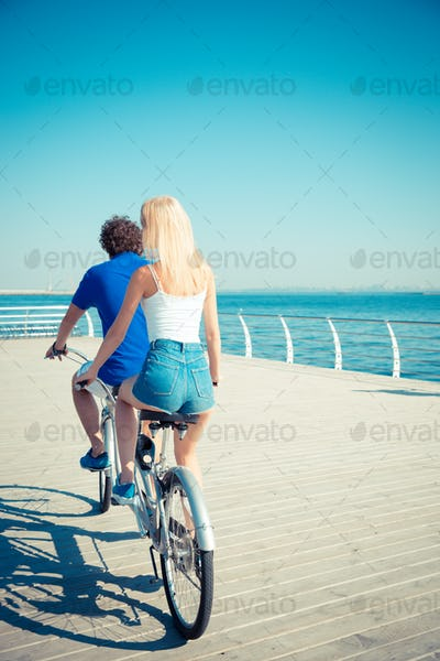 ?an and woman riding in tandem bicycle