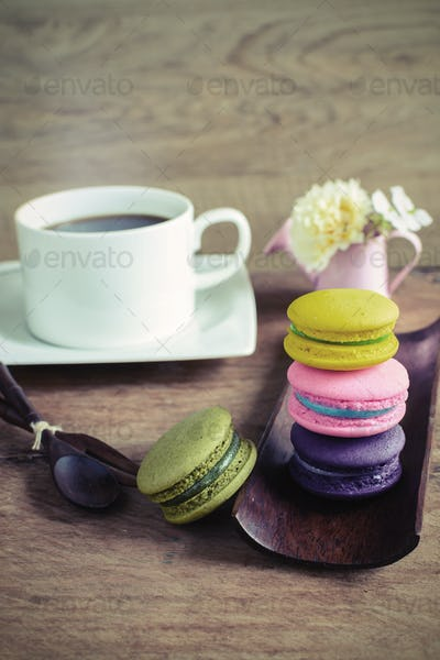Colorful macaroons and a cup of coffee on wooden table