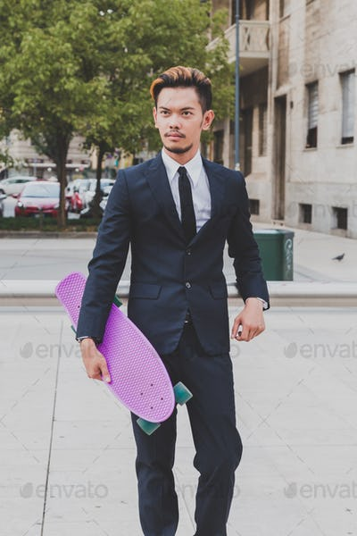Young handsome Asian model posing with his skateboard