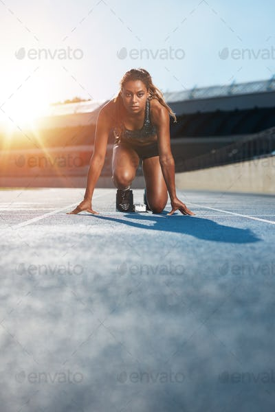Young female sprinter in start position on racetrack
