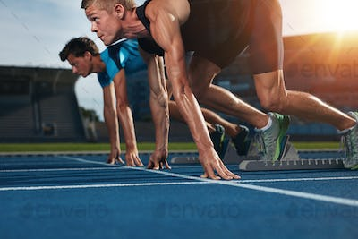 Fit athlete running race in athletics racetrack on a sunny day