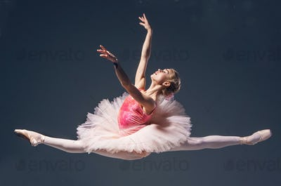 Beautiful female ballet dancer jumping on a gray background