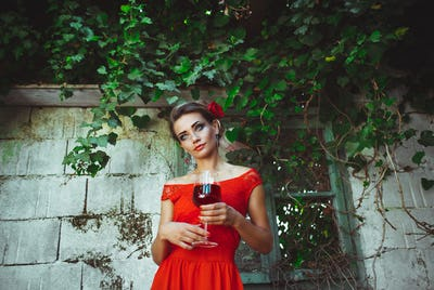 Beautiful woman in red dress standing with glass of wine in the