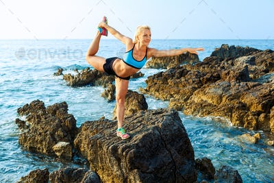 Athlete woman doing sport exercising on the rocks by the sea