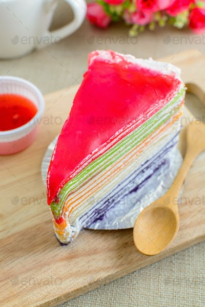 Rainbow cake on wooden board with cup of coffee
