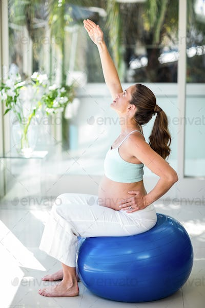 Side view of pregnant woman sitting on ball at home