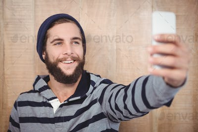 Happy hipster with hooded shirt taking selfie against wooden wall