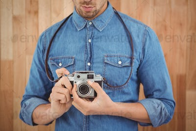 Mid section of man adjusting camera lens against wooden wall in office