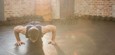 Handsome man doing wide arm push ups at the gym
